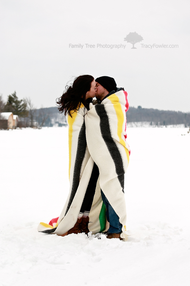 couple kissing on a frozen lake wrapped in a Hudson
